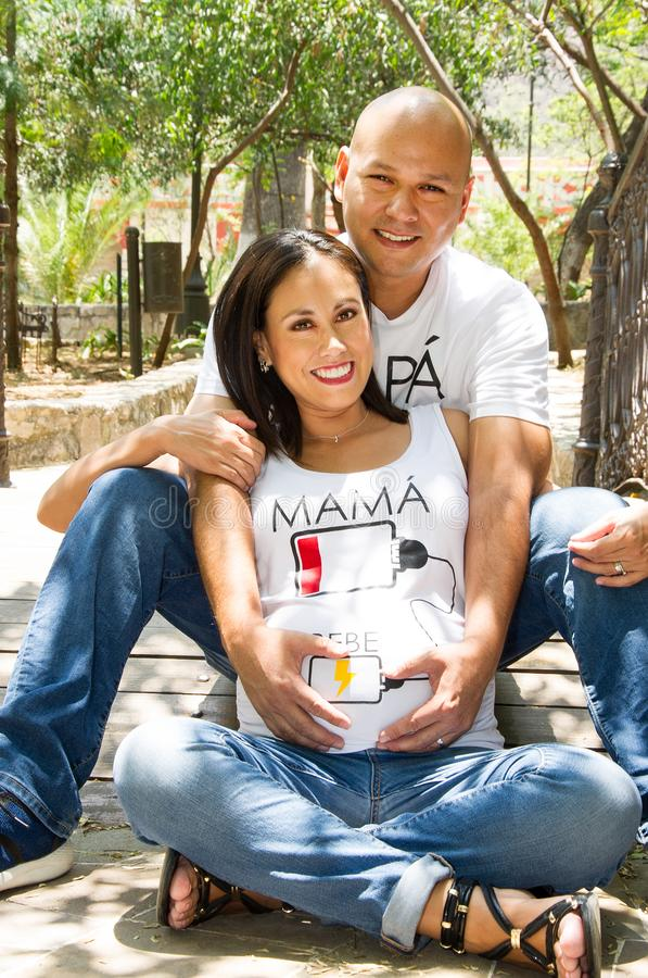 Mexican lovely couple. Pregnant couple hugging and kissing tenderly in a bridge in a  park royalty free stock photo