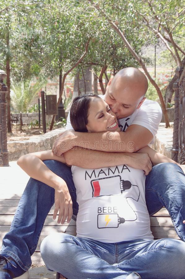 Mexican lovely couple. Pregnant couple hugging and kissing tenderly in a park royalty free stock photos