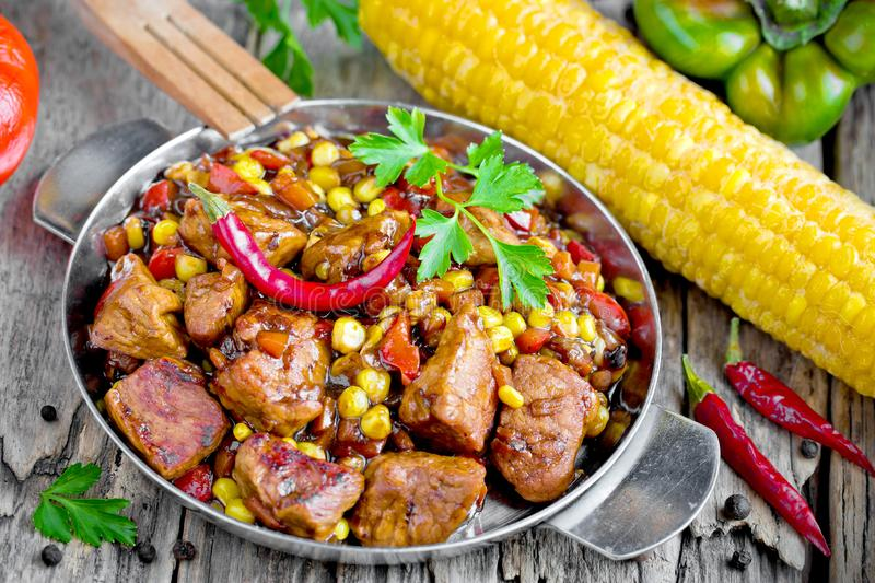 Mexican meat - pork stewed with vegetables corn, pepper, onion, carrot royalty free stock photo