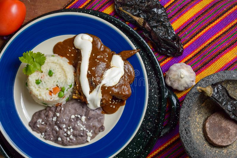 Mexican mole sauce with chicken. Rice and black refried beans. Served alongside ingredients like chocolate and chilies. Traditional food from Oaxaca and other royalty free stock photography
