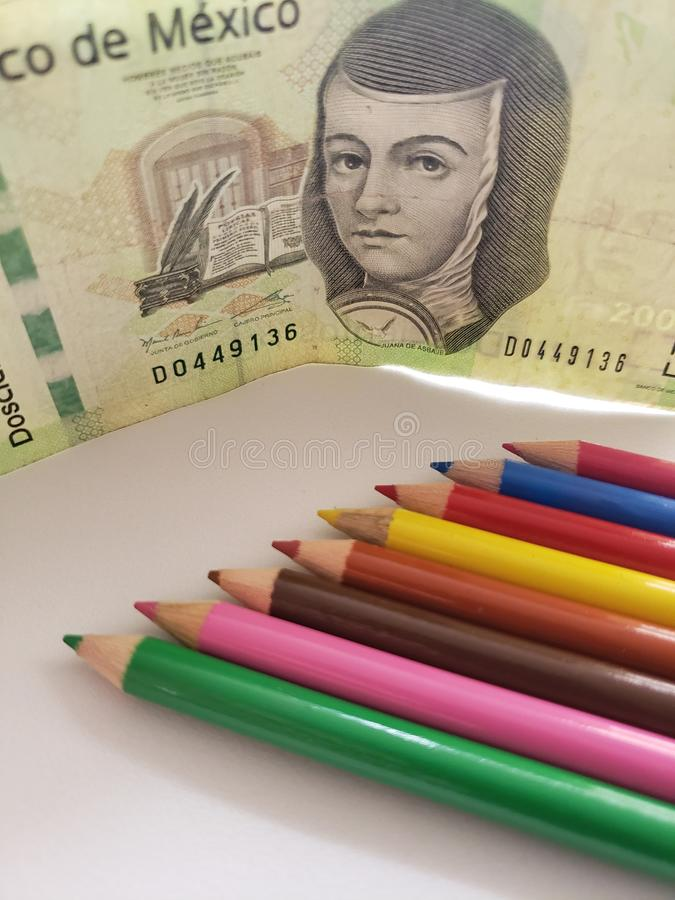 Mexican money and color pencils on the white background. Pencil, wood, colorful, colored, multicolored, education, school, college, object, tools, material stock images