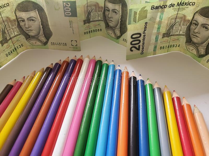 Mexican money and color pencils on the white background. Pencil, wood, colorful, colored, multicolored, education, school, college, object, tools, material stock image