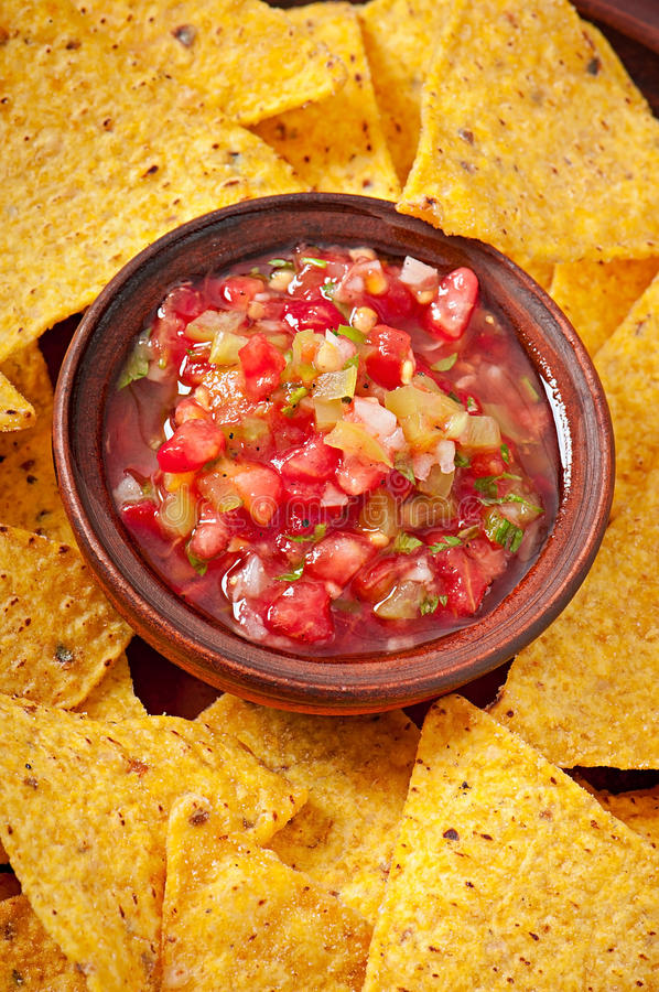 Mexican nacho chips and salsa dip. In bowl on wooden background stock photo