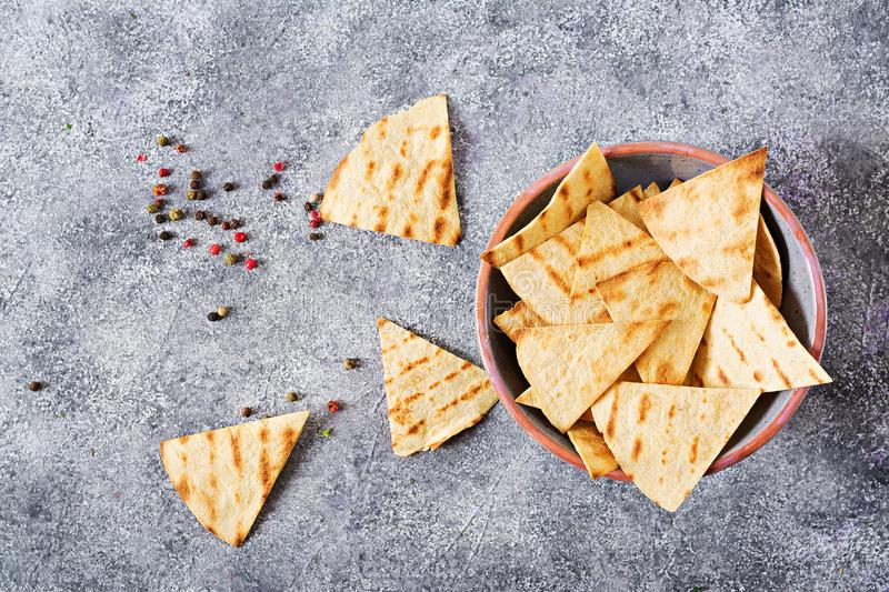 Mexican nachos on a light background. Mexican nachos on a light background in the grey plate. Top view royalty free stock image