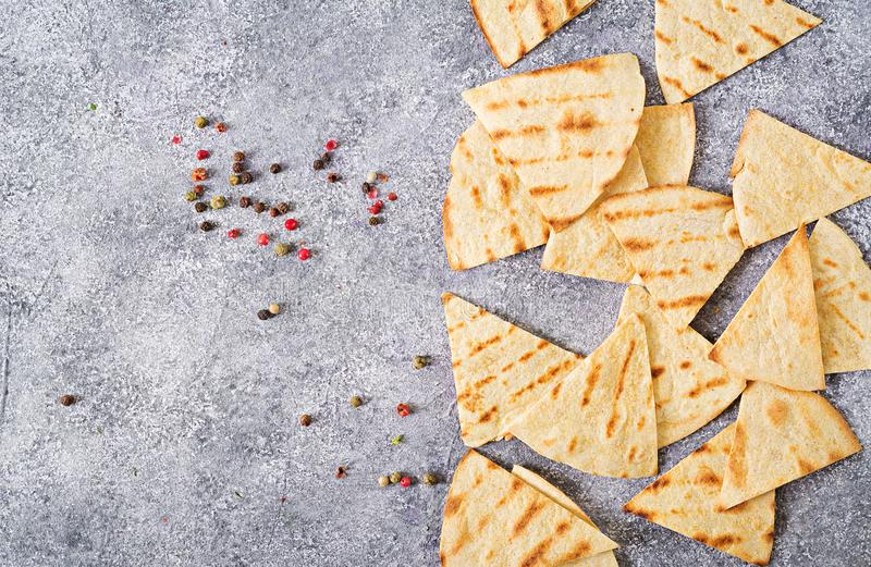 Mexican nachos on a light grey background. Mexican nachos on a light grey background with pepper. Top view stock image