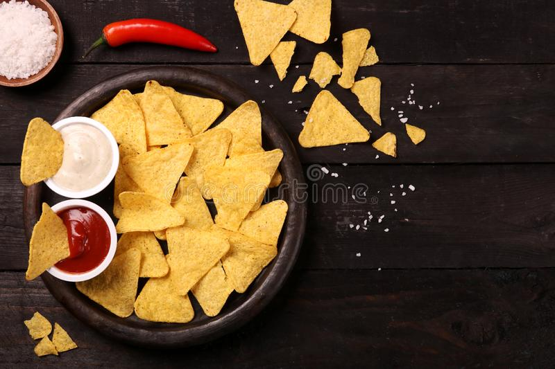 Mexican nachos in Wooden Bowl tortilla chips with chilli sauce, salsa and cheese dip, top view and Black Background stock images