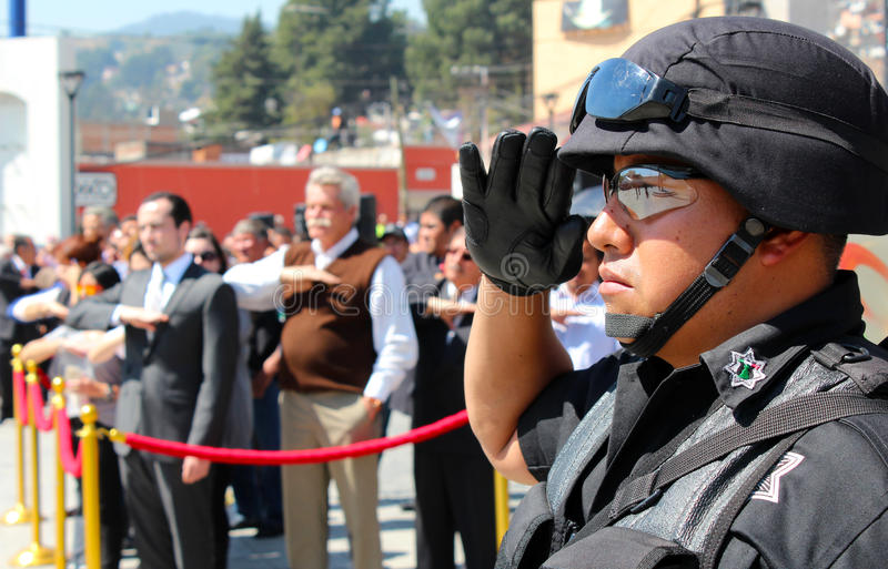 Mexican officer salutes to mexican flag. A special forces police officer salutes to the mexican flag showing respect to it in a ceremony royalty free stock images