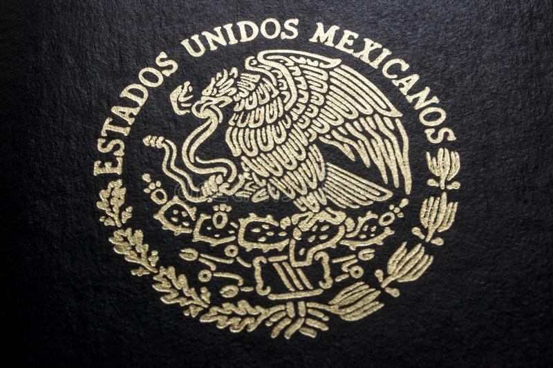 Mexican passport in a black background. Front face of a Mexican passport. Black background. Close-up of its national coat of arms royalty free stock images
