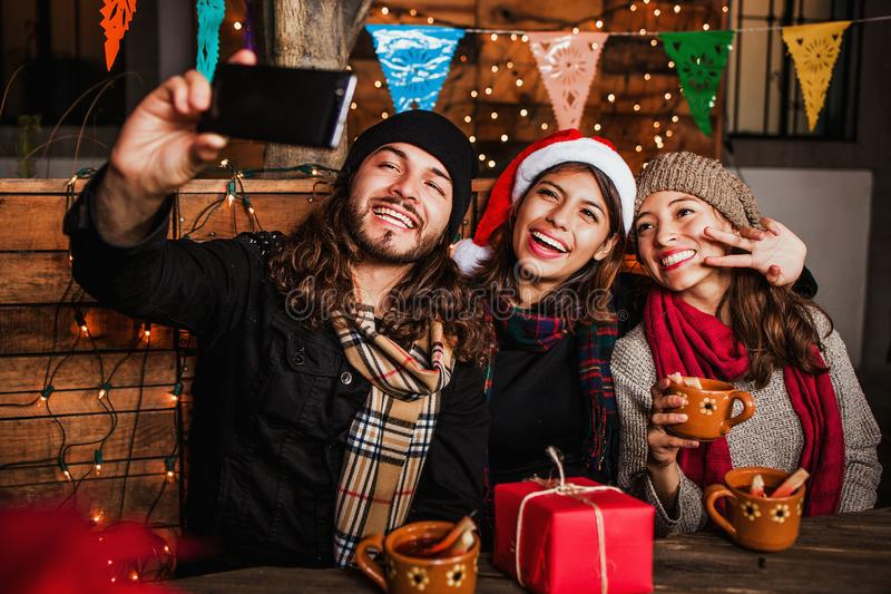 Mexican Posada friends celebrating Christmas in Mexico and taking a photo selfie. Mexican Posada friends celebrating Christmas in Mexico city and taking a photo stock image