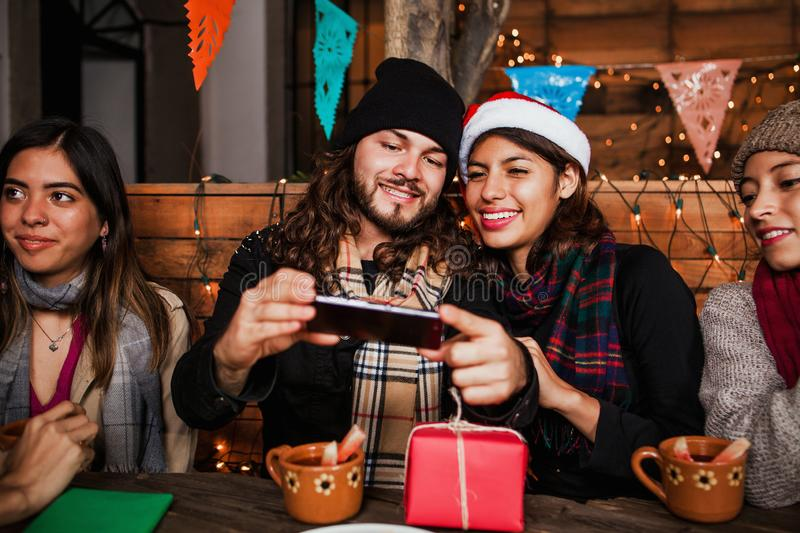 Mexican Posada friends celebrating Christmas in Mexico and having fun taking a photo royalty free stock images