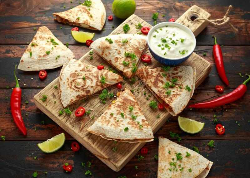 Mexican quesadilla with chicken, corn, black beans, cheese, vegetables, lime and yogurt sauce on wooden board stock photo