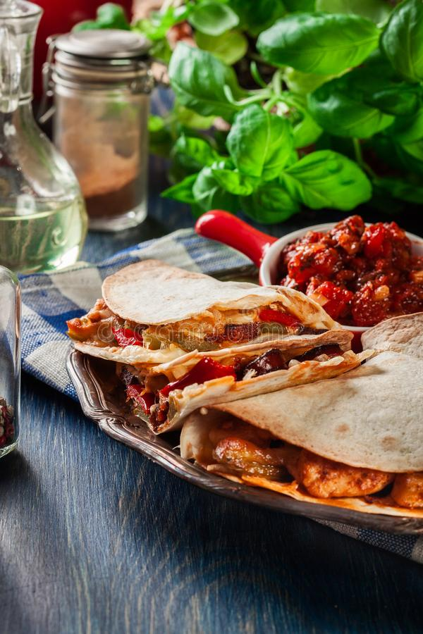 Mexican Quesadilla with chicken, sausage chorizo and red pepper. Served with salsa stock photo