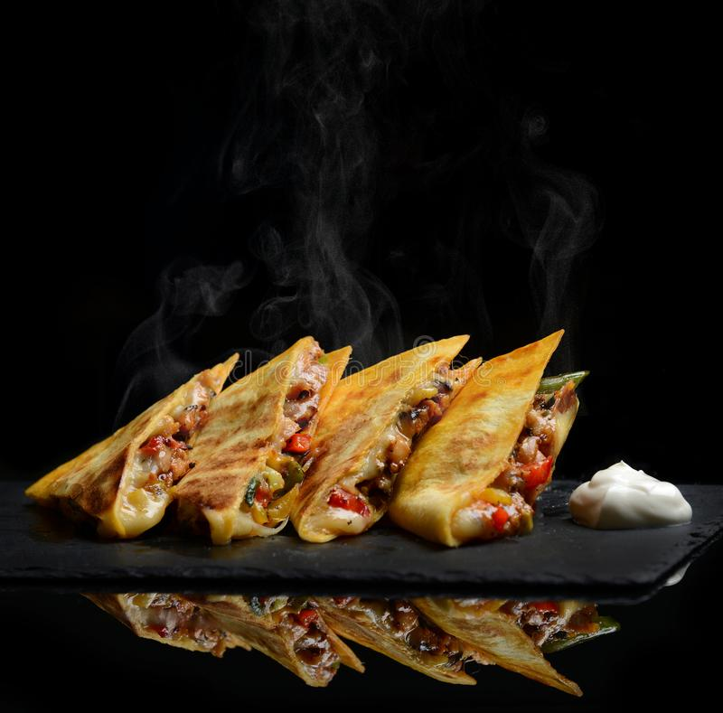 Mexican Quesadilla wrap with chicken sweet pepper sour cream and salsa hot with steam smoke stock images