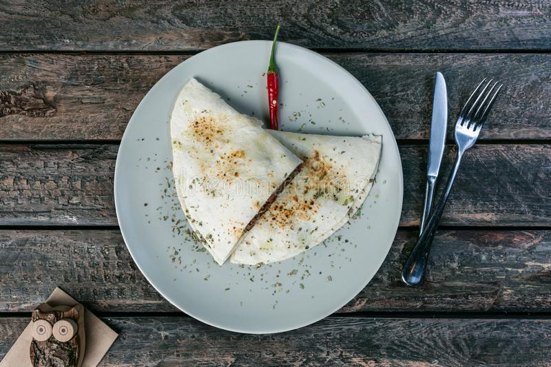 Mexican quesadillas, tortilla wraps with beef bacon, champignons, cream cheese, served with cutlery on the wooden royalty free stock images
