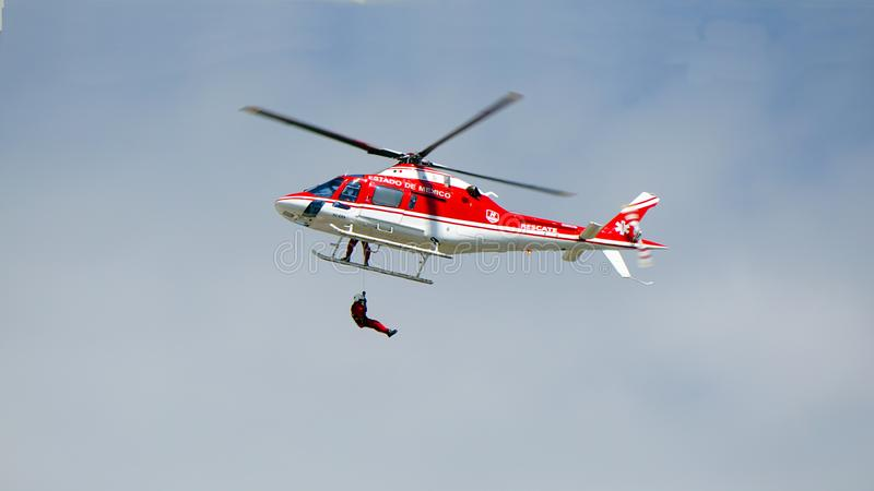 Air rescue man. Mexican rescue helicopter flies with a man hanging in the bottom of it, rescue man hangs with a special rope in a red and white helicopter royalty free stock photo