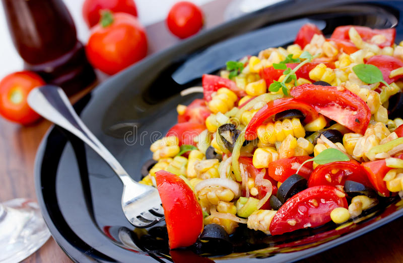 Mexican salad of tomatoes, corn, olives, onion and pepper royalty free stock photography