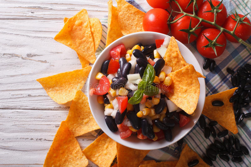 Mexican salsa with beans and corn chips nachos. horizontal top. Mexican salsa with beans in a bowl and corn chips nachos on the table close-up. horizontal view royalty free stock image