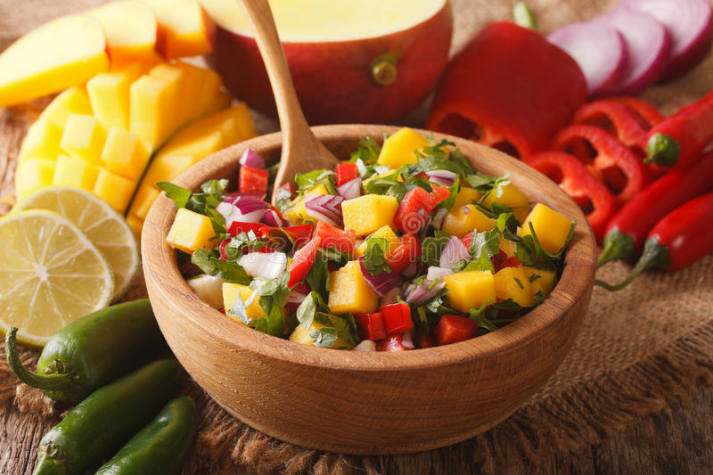Mexican salsa with mango, pepper, jalapeno, cilantro and onions. In a bowl close-up. horizontal stock photography