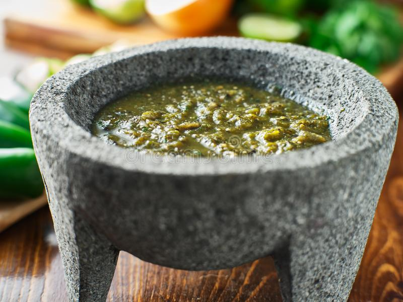 Mexican salsa verde in traditional stone molcajete royalty free stock photo