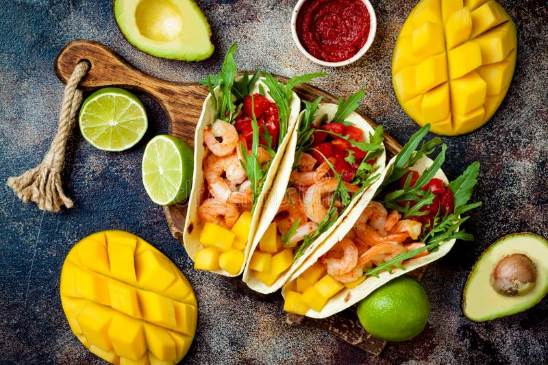 Mexican shrimp tacos with avocado, tomato, mango salsa on rustic stone table. Recipe for Cinco de Mayo party. stock images
