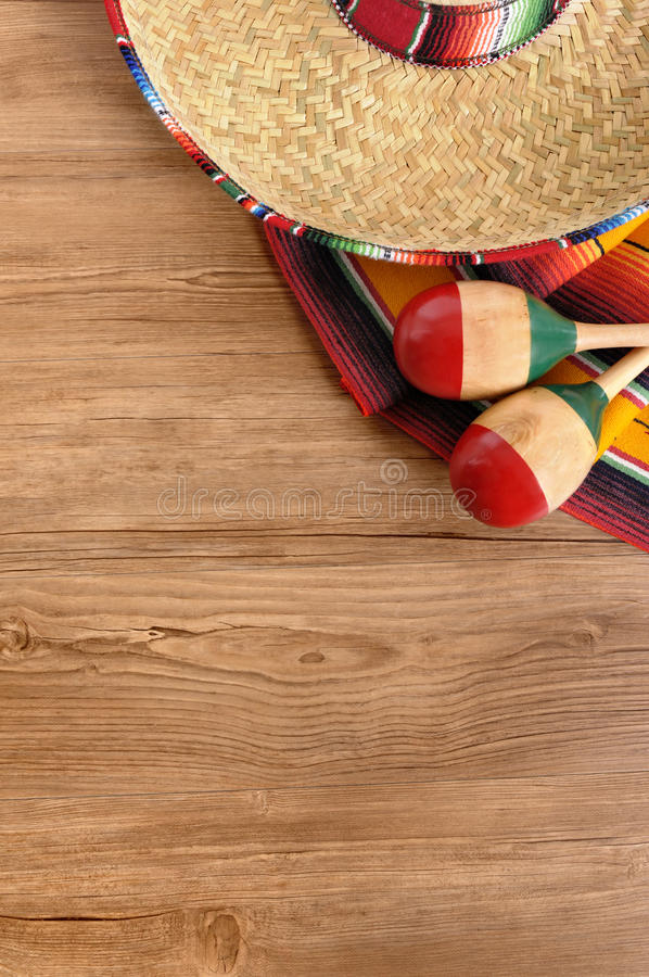 Mexico : Mexican background, sombrero, wood, copy space vertical. Mexican background with sombrero straw hat, maracas and traditional serape blanket or rug on a royalty free stock photo