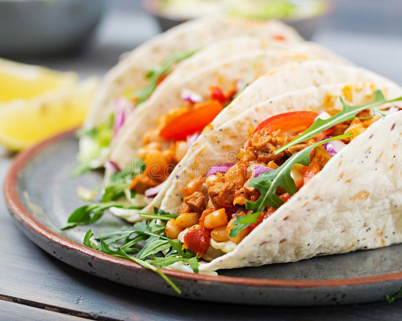 Mexican tacos with beef, beans in tomato sauce stock photo