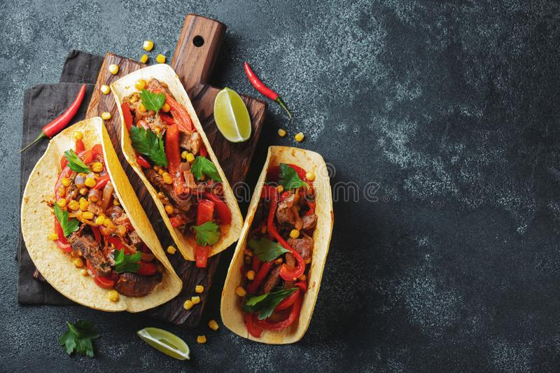 Mexican tacos with beef, vegetables and salsa. Tacos al pastor on wooden board on black background. Top view with copy space royalty free stock photos