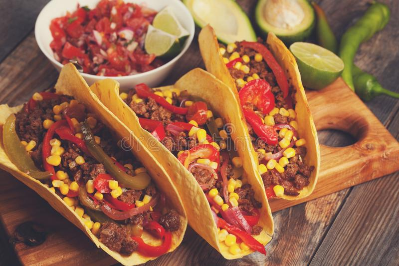 Mexican tacos with minced beef, vegetables and salsa. Tacos al pastor on wooden rustic background.  stock photo