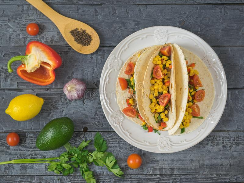 Mexican tacos on a plate on a wooden table and ingredients. The view from the top. royalty free stock photo