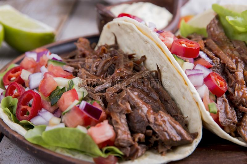 Mexican tacos with roasted beef ,sauce and salsa tomato stock images
