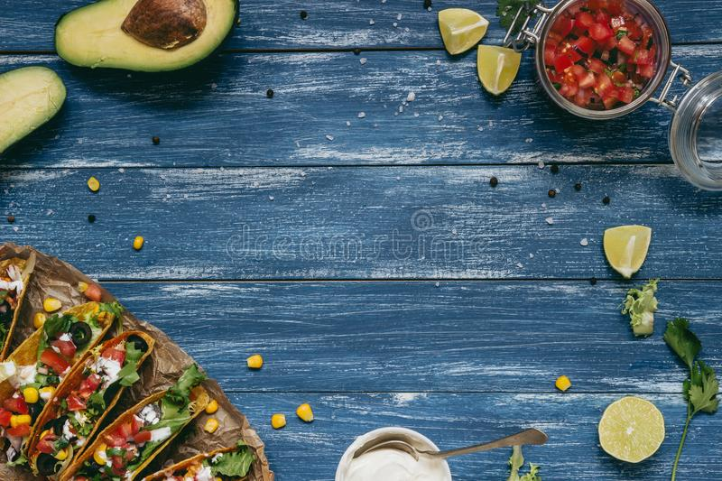 Mexican tacos with salsa and avocado on the wooden blue background, top view. Copy space stock image