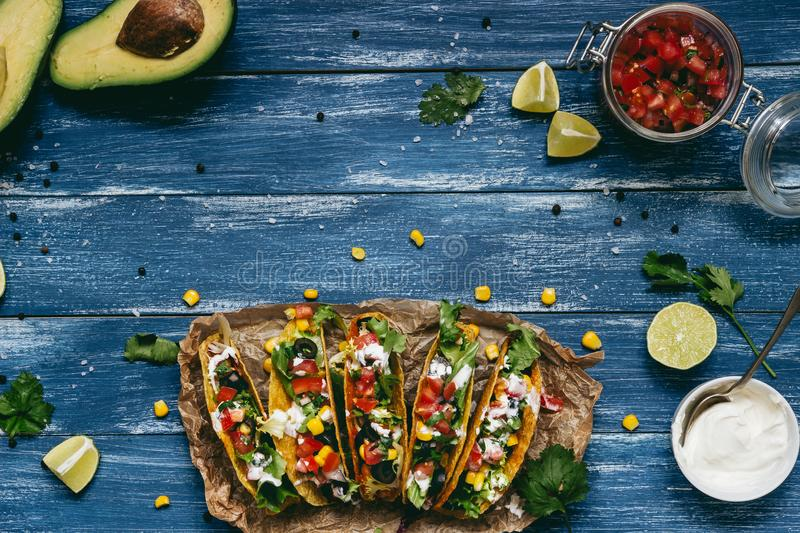 Mexican tacos with salsa and avocado on the wooden blue background, top view.  stock photos