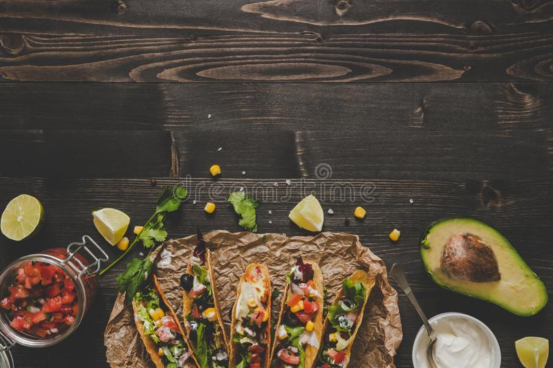 Mexican tacos with vegetables, salsa and avocado on the wooden background, top view. Copy space stock photo