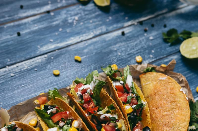 Mexican tacos with vegetables on the wooden blue background, close up. Selective focus with copy space royalty free stock images