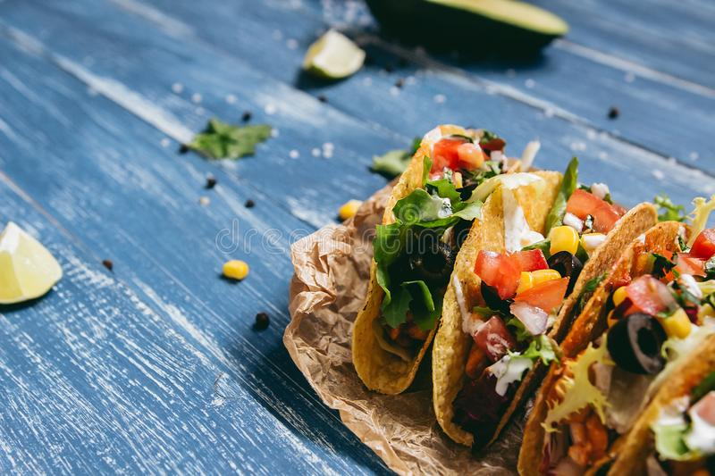 Mexican tacos with vegetables on the wooden blue background, close up. royalty free stock images