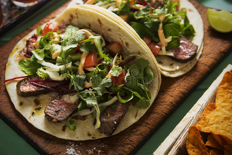 Mexican tortillas with beef steak and salad. On blue table royalty free stock image