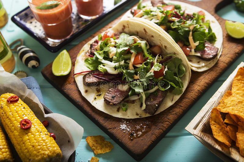 Mexican tortillas with beef steak and salad. On blue table stock photos