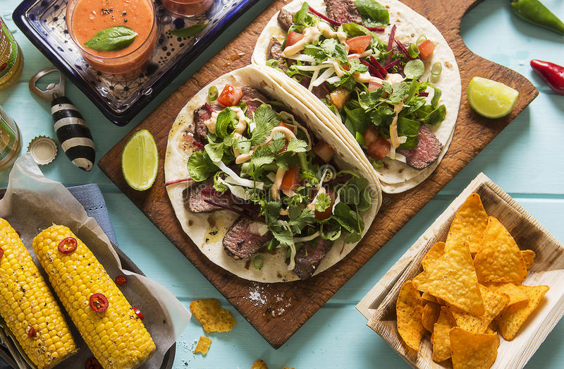 Mexican tortillas with beef steak and salad. On blue table stock images