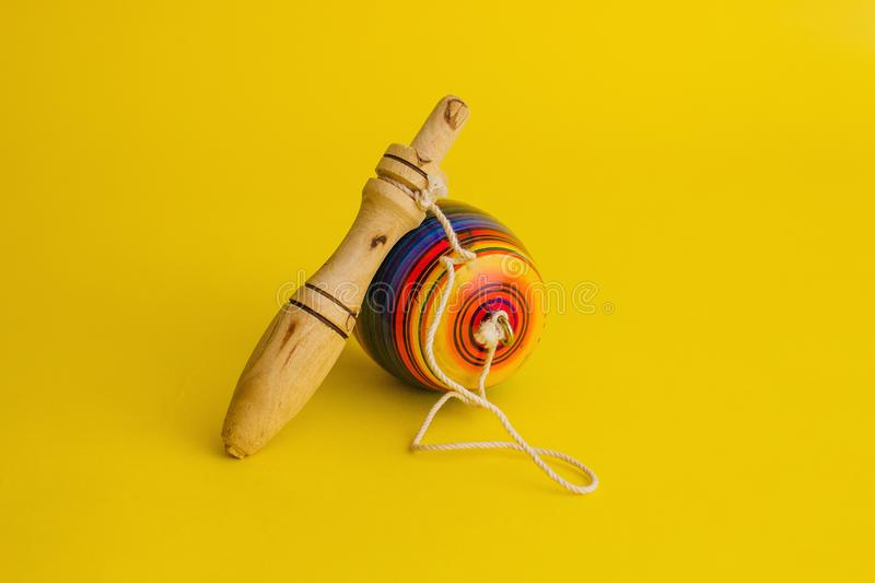 Mexican toys from Wooden, balero, yoyo and trompo in Mexico on a yellow background stock photo