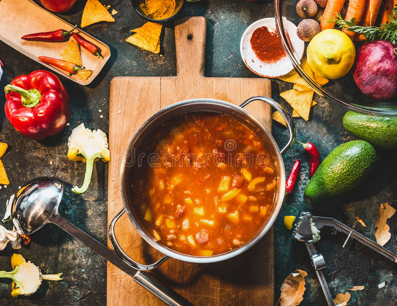 Mexican vegetarian bean soup in cooking pot with ladle on rustic kitchen table ingredients and cutting board, top view. Vegan or vegetarian healthy food stock images