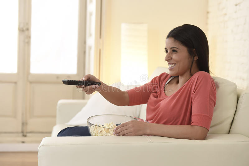 Mexican woman watching television at sofa couch happy excited enjoying romantic film. Young beautiful Spanish woman home alone watching television smiling royalty free stock photo
