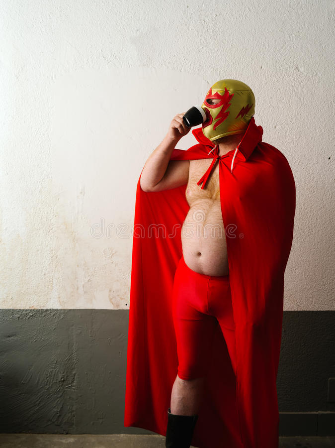 Mexican wrestler drinking coffee royalty free stock images
