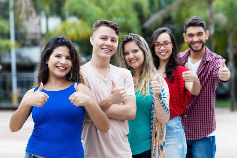 Mexican young adult woman with group of friends in line stock photography