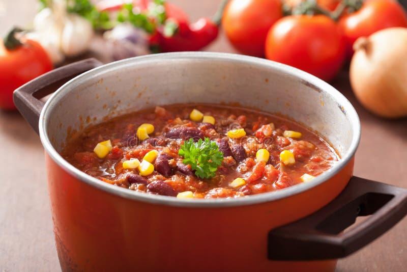 Mexicano chili con carne en pote rústico rojo con los ingredientes imagen de archivo libre de regalías