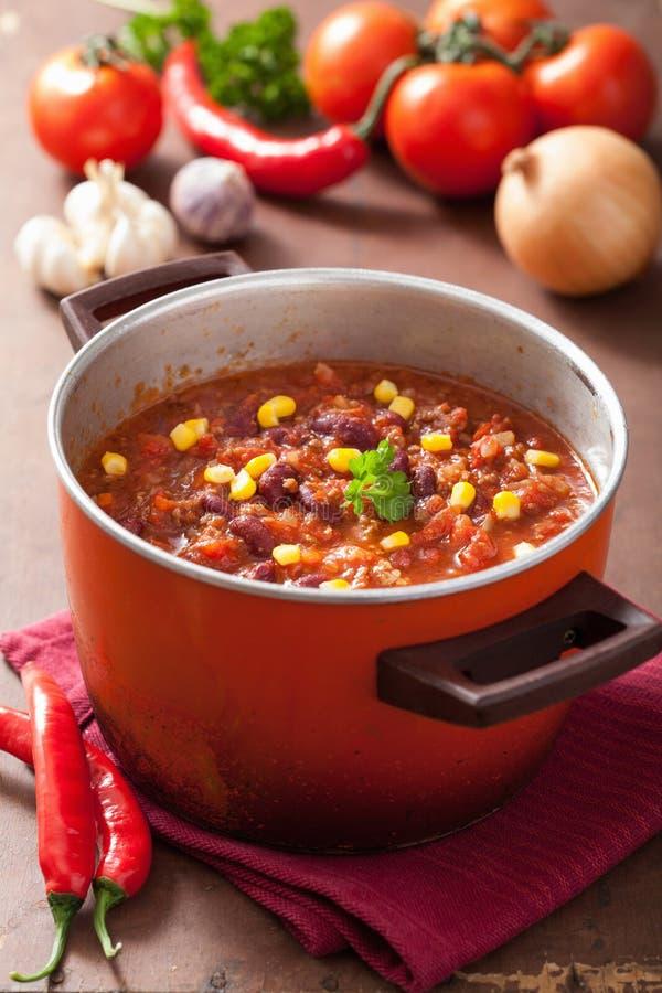 Mexicano chili con carne en pote rústico rojo con los ingredientes fotografía de archivo libre de regalías