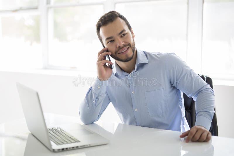 Mexicansk attraktiv affärsman på hans 30-tal som arbetar på den moderna inrikesdepartementet med datorbärbara datorn royaltyfri fotografi