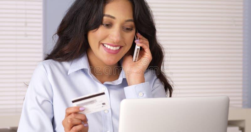 Mexicansk kvinna som gör lyckligt köpet över telefonen fotografering för bildbyråer
