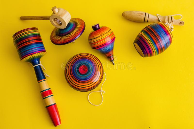 Mexicansk leksaker från trä, balero, yoyoen och trompo i Mexico på en gul bakgrund arkivfoto