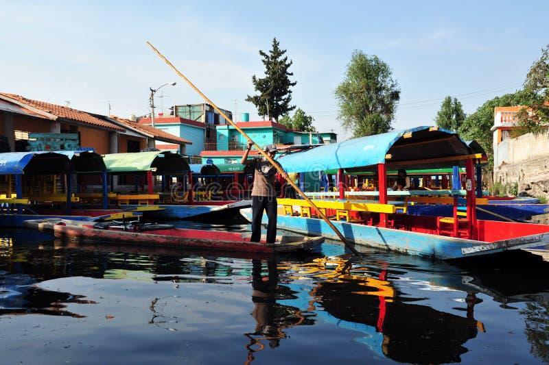 Mexicansk man som seglar färgrika mexicanska gondoler på Xochimilcos som svävar trädgårdar nära Mexico - stad, Mexico royaltyfri fotografi