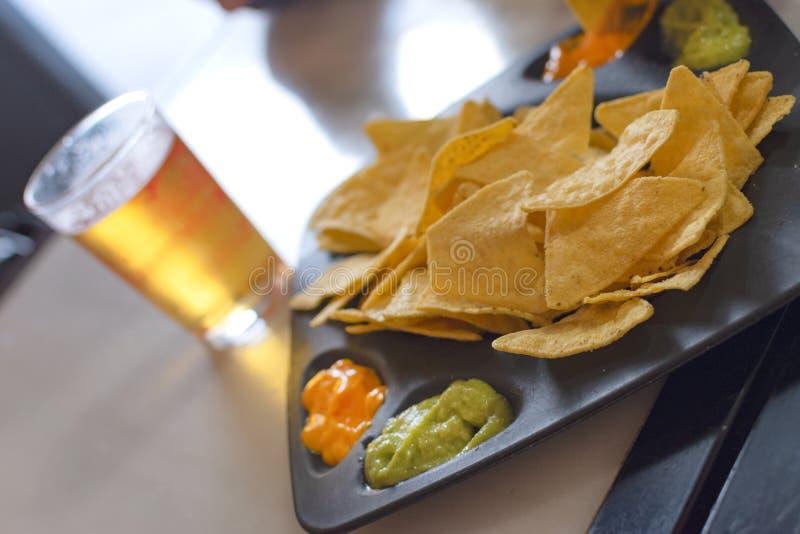 Mexicansk nachosmaträtt med guacamolesås arkivbild